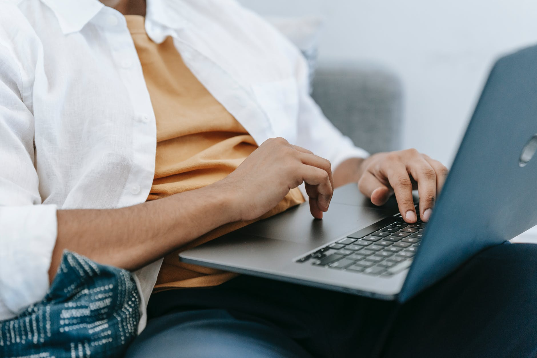crop remote employee typing on laptop at home