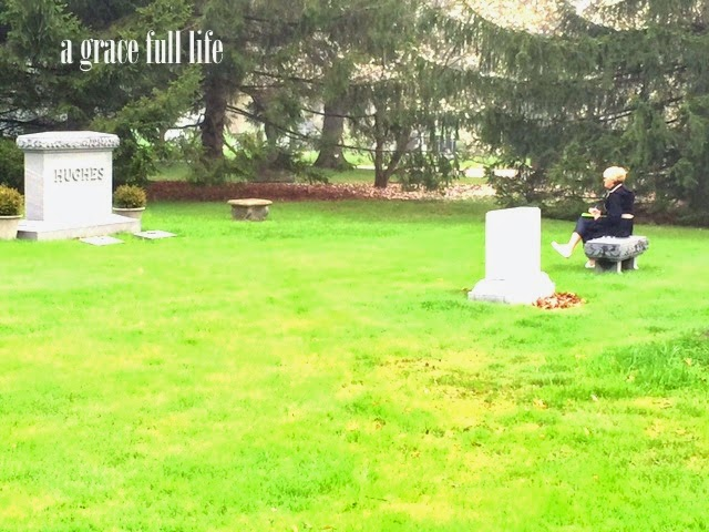 writer sitting at John Hughes grave site